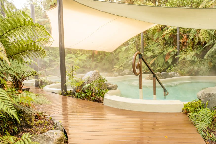 outdoor hot spring pool covered by a canopy with a wooden walkway