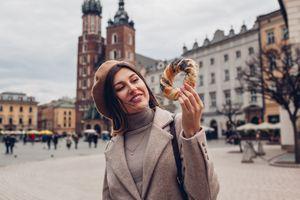 Tourist woman eats bagel obwarzanek traditional polish cuisine snack on Market square in Krakow. Travel Europe
