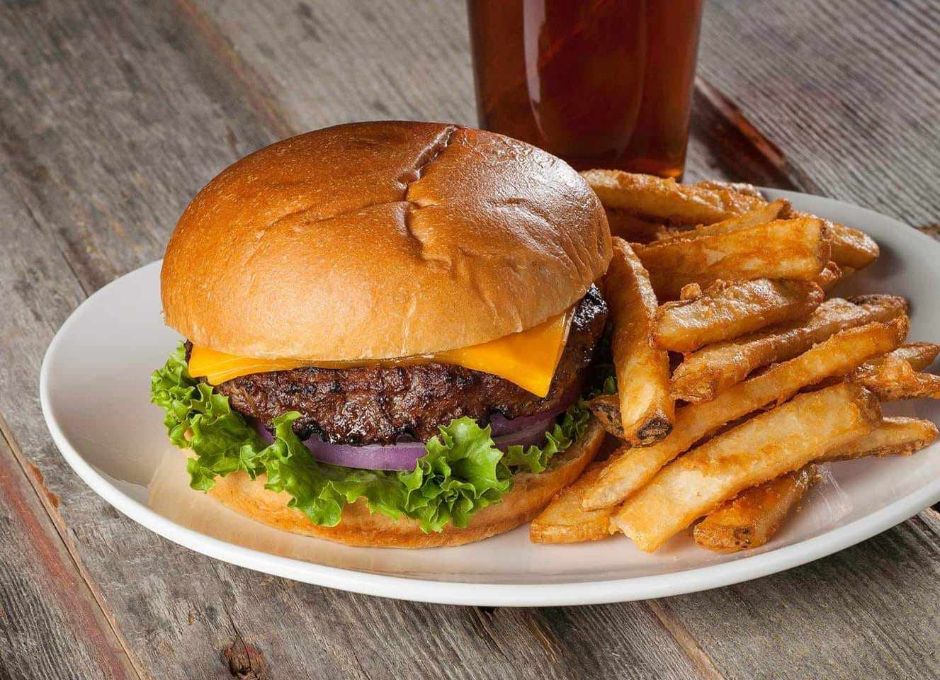 cheeseburger on a plate with large-cut french fries