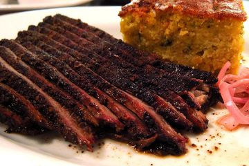 Sliced brisket on a plate with a tall slice of cornbread