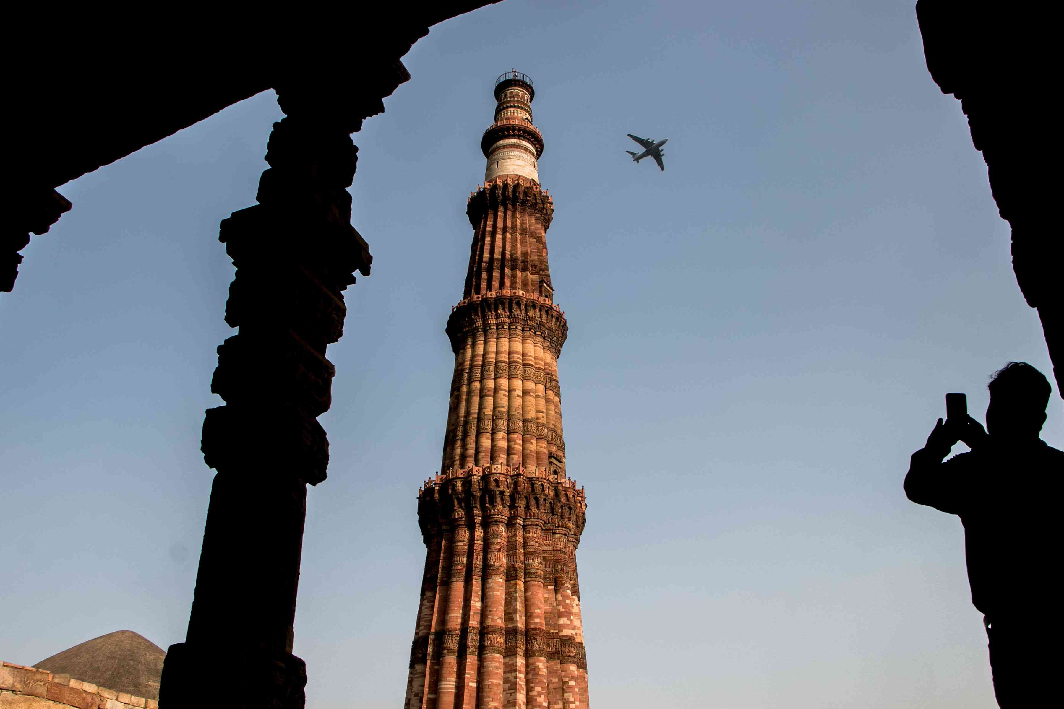 A man taking a photo of Qutab Minar with a plane flying by it