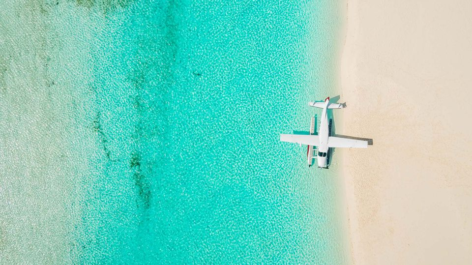 Overhead shot of a seaplane on the beach shoreling with bright blue water and white sand beaches