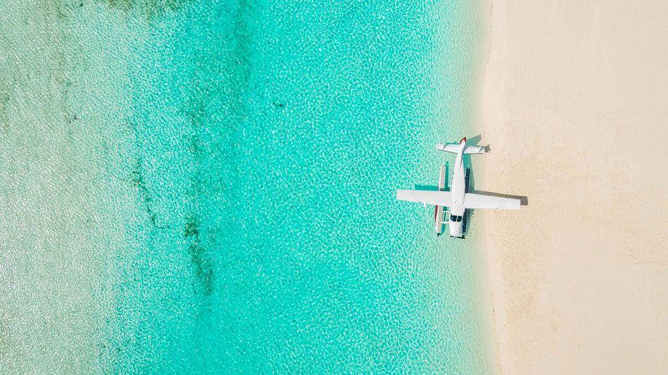 Fotografía cenital de un hidroavión en la orilla de la playa con agua azul brillante y playas de arena blanca