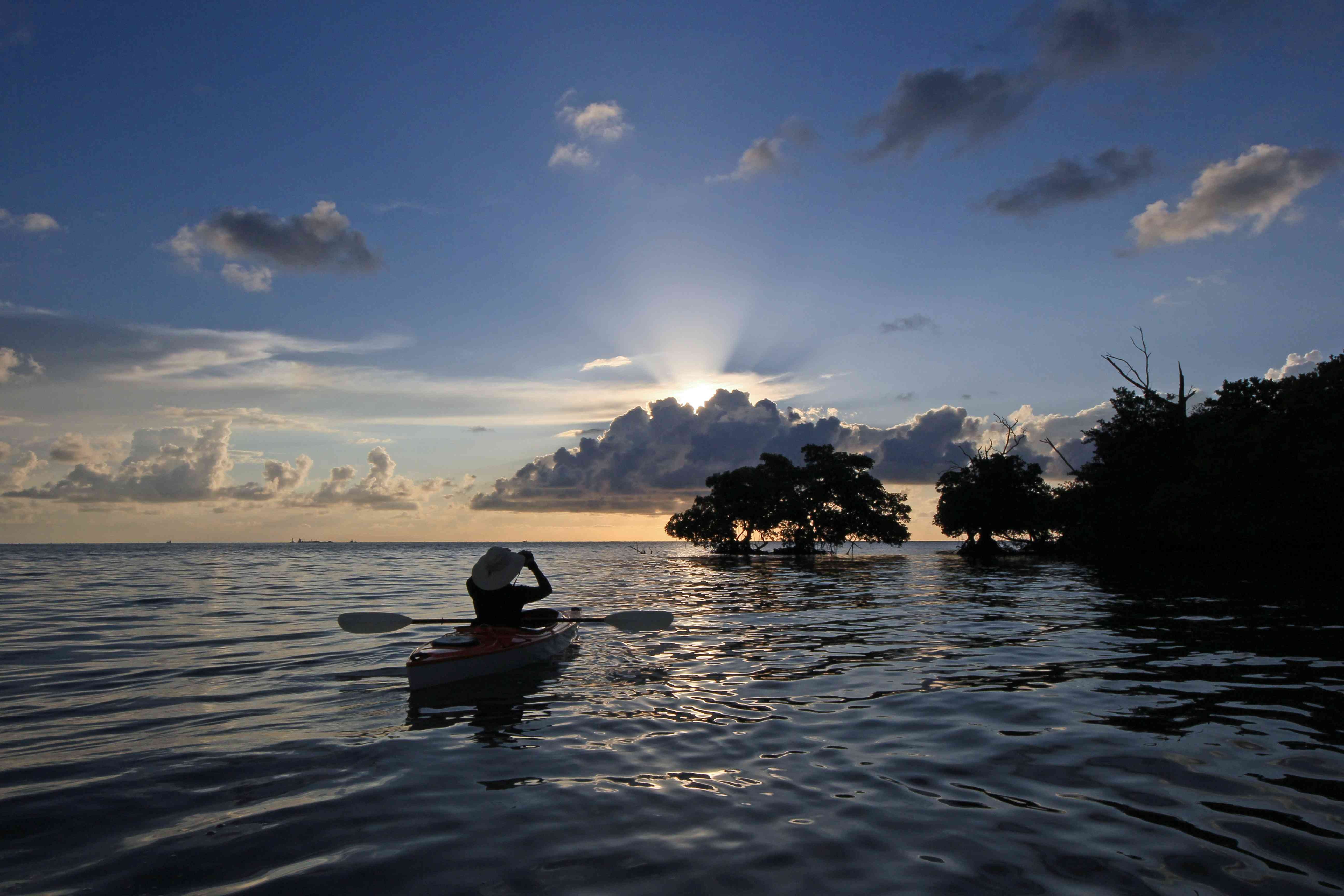 Female kayaker photographs the sunrise and sun rays amidst the mangroves of Bear Cut off Key Biscayne.