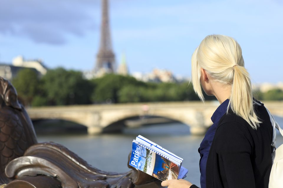 A woman with a Paris travel guidebook ni her hands stares at the Eiffel Tower in the distance