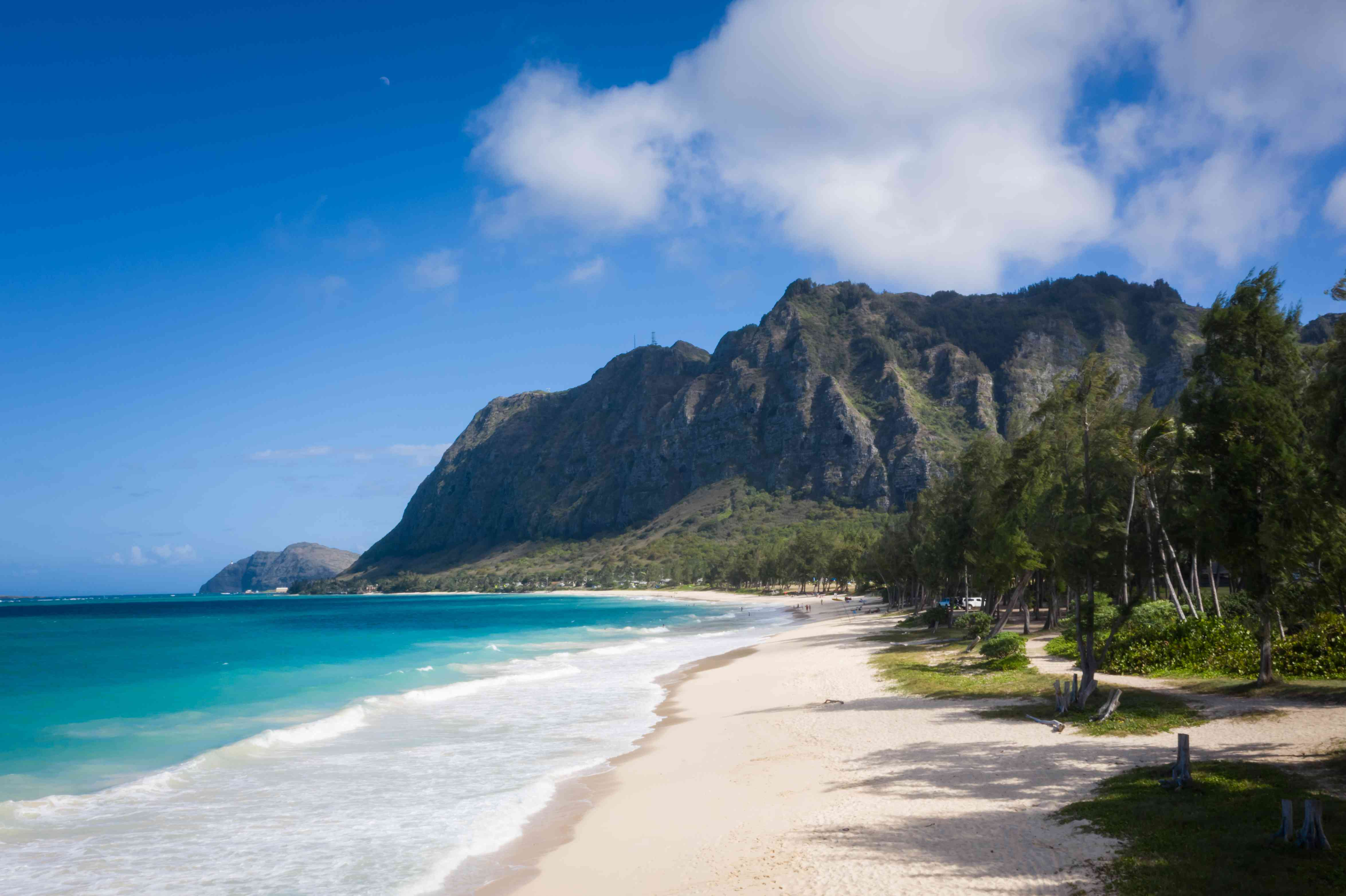 Sunny beach in Oahu Hawaii with a mountain in the background
