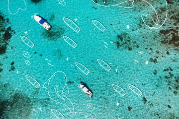 Bird's eye view of the ocean around Belize with boats. Illustrated white lines showing boats, swimmers, and larger than life fish