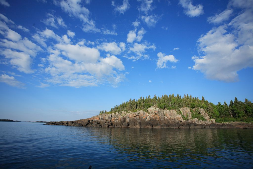 On the lake looking at a rocky coast with evergreen trees