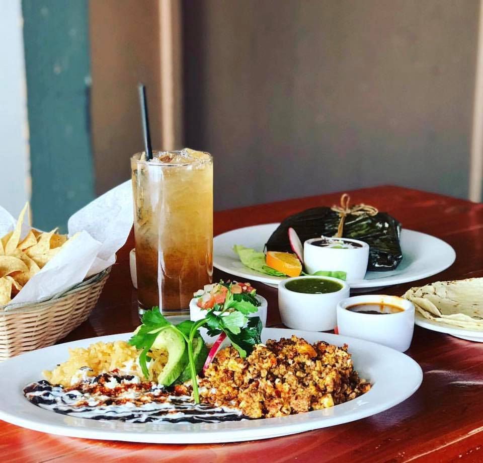 Oaxacan cuisine on a table with a basket of torilla chips and a brown drink with ice. One place has black molé with white rice, and chicken garnished with cilantro and two avocado slices. Behind this plate and two small containers of green and brown sauces is a place with a banana leaf-wrapped tamale
