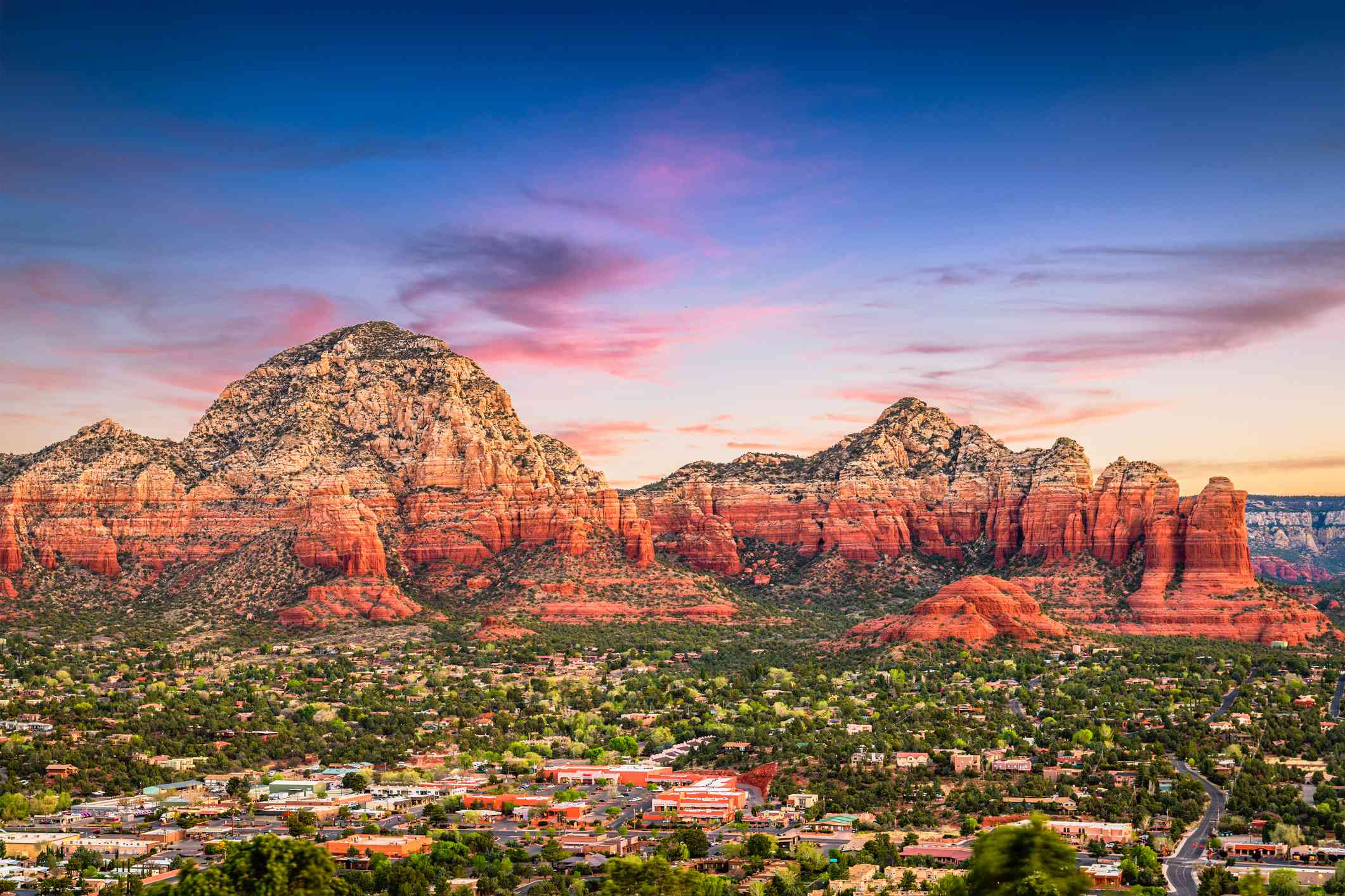 large red rock mountains at dusk with the city of Sedona at the base