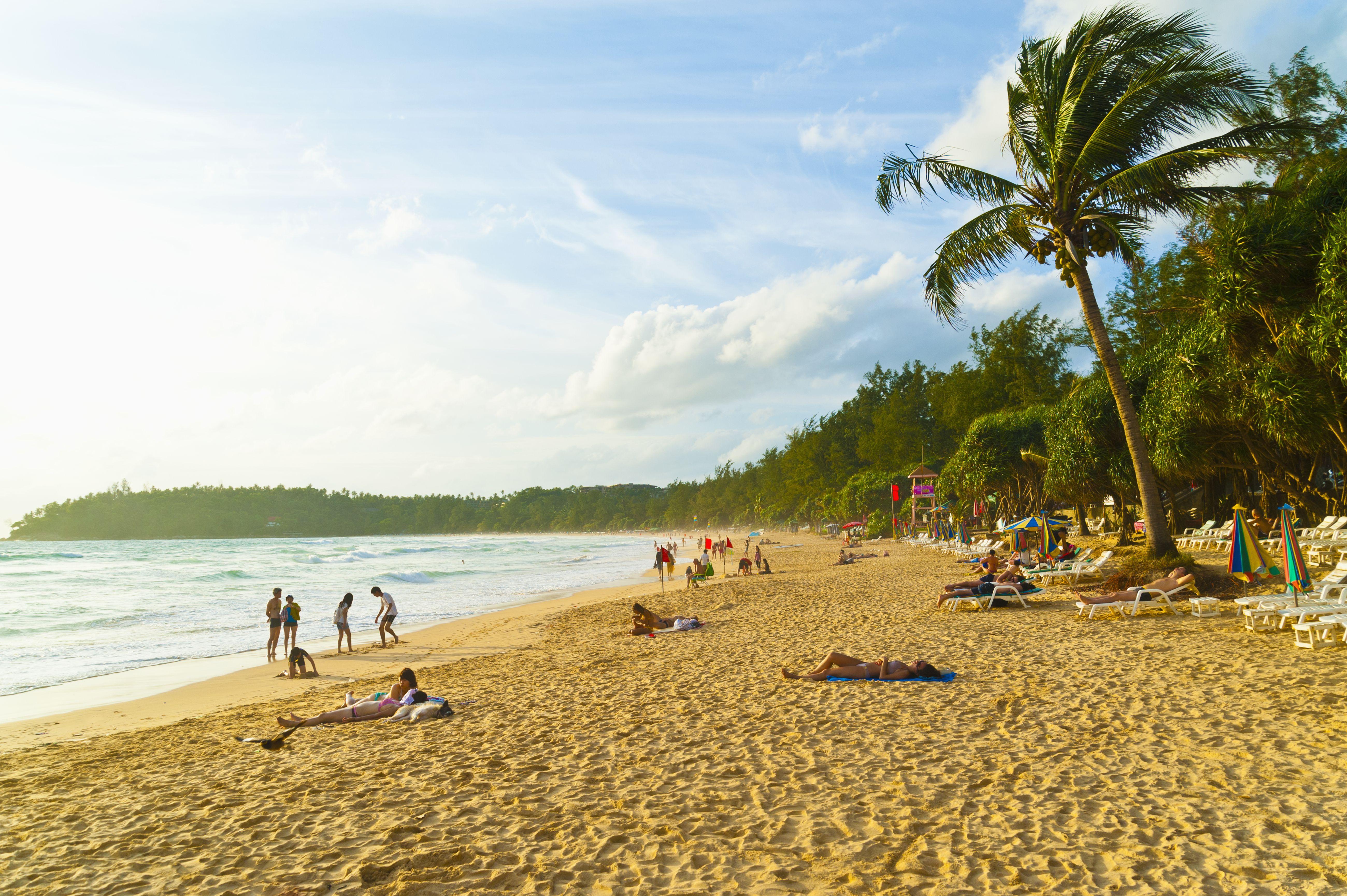 Sunbathers on golden sand along Kata Beach