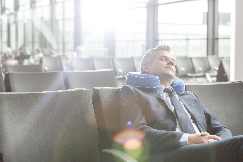 Businessman sleeping at airport departure lounge