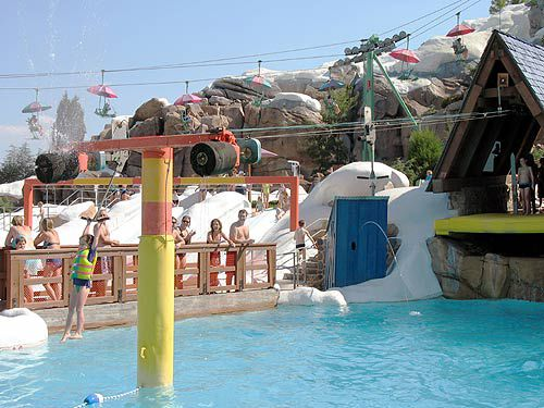 Kids ride a t-bar across a zip line and drop into the water at Blizzard Beach.