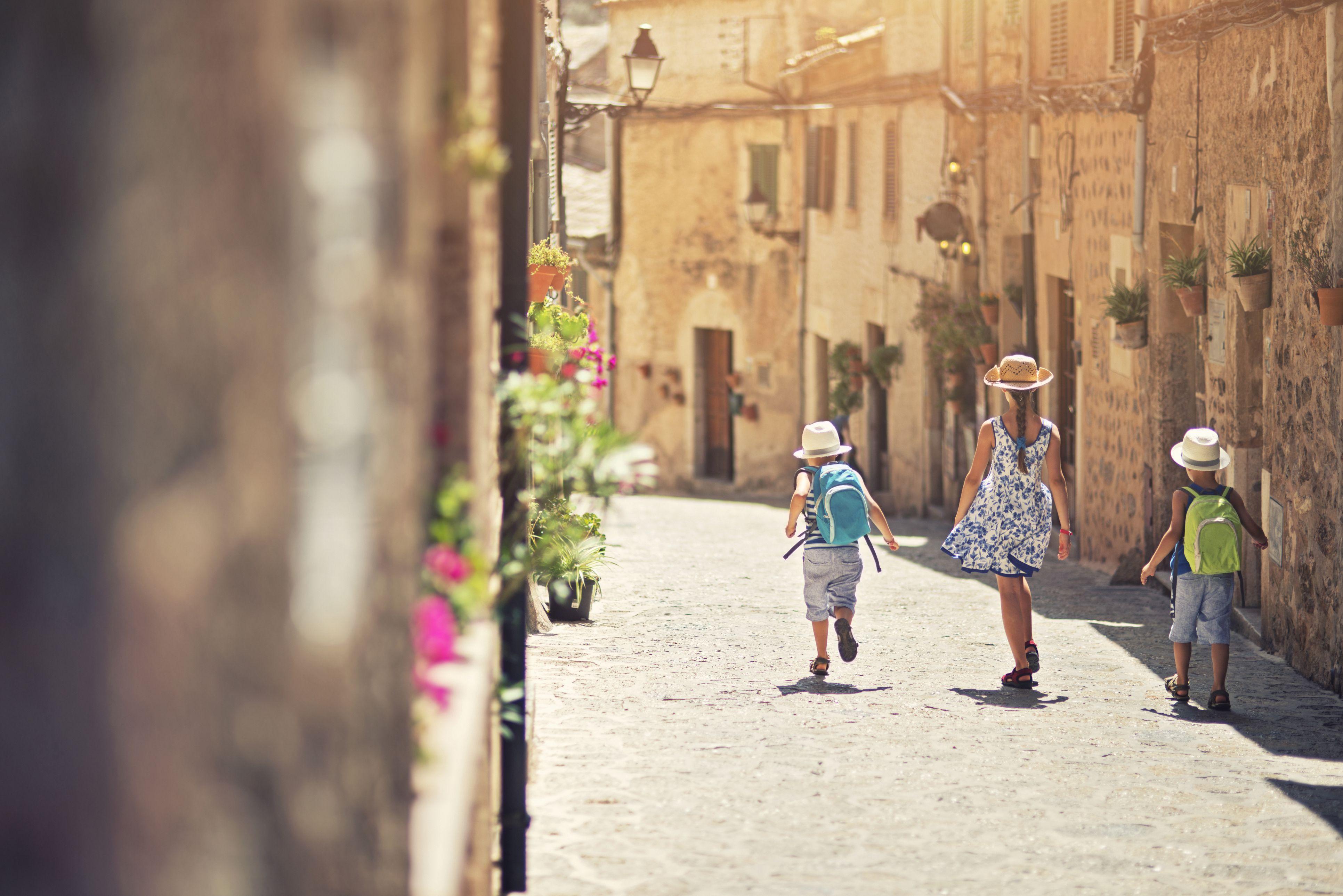 Kids walking in mediterranean street.