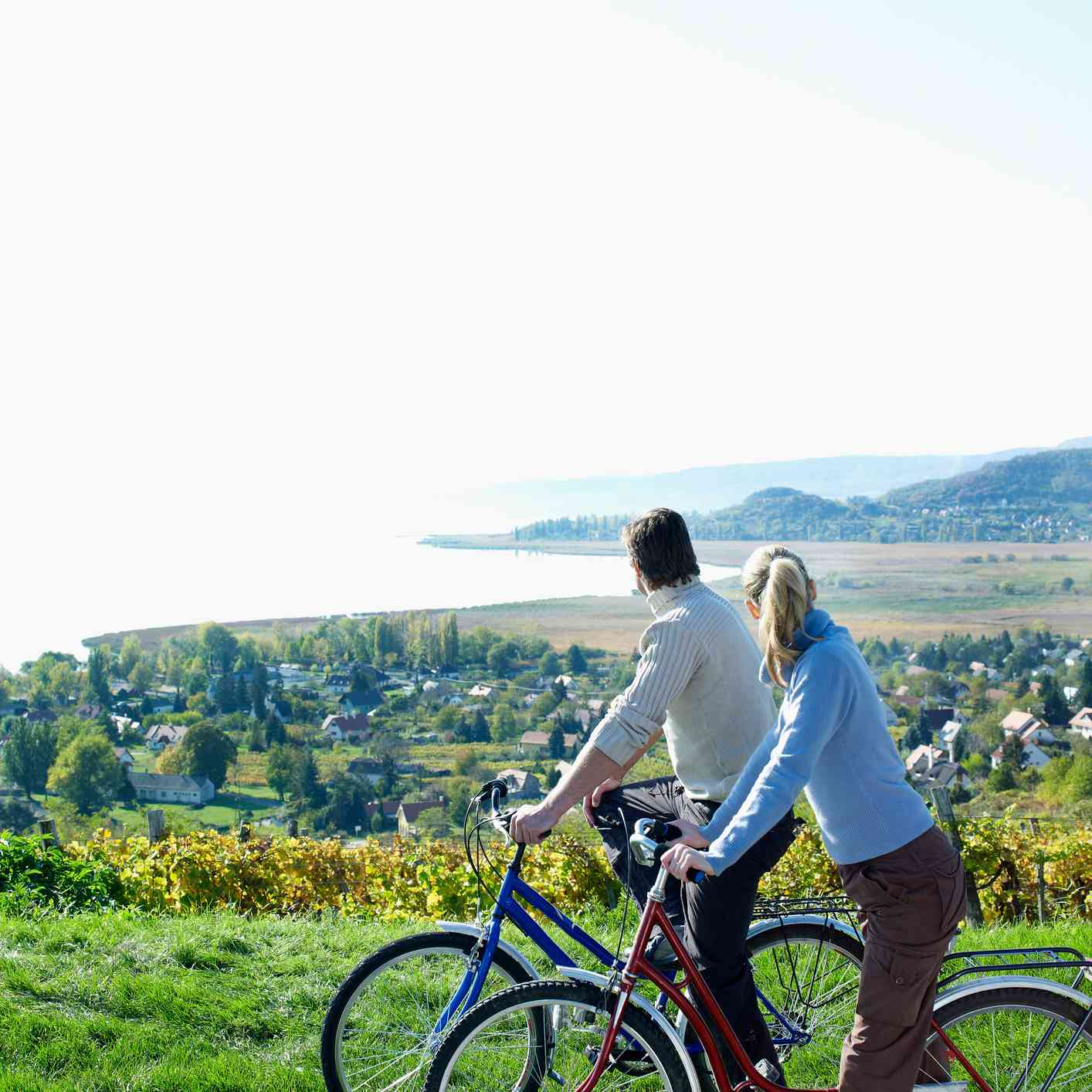 Cycling couple looking out over elevated view of vineyards and Lake Balaton, Budapest, Hungary
