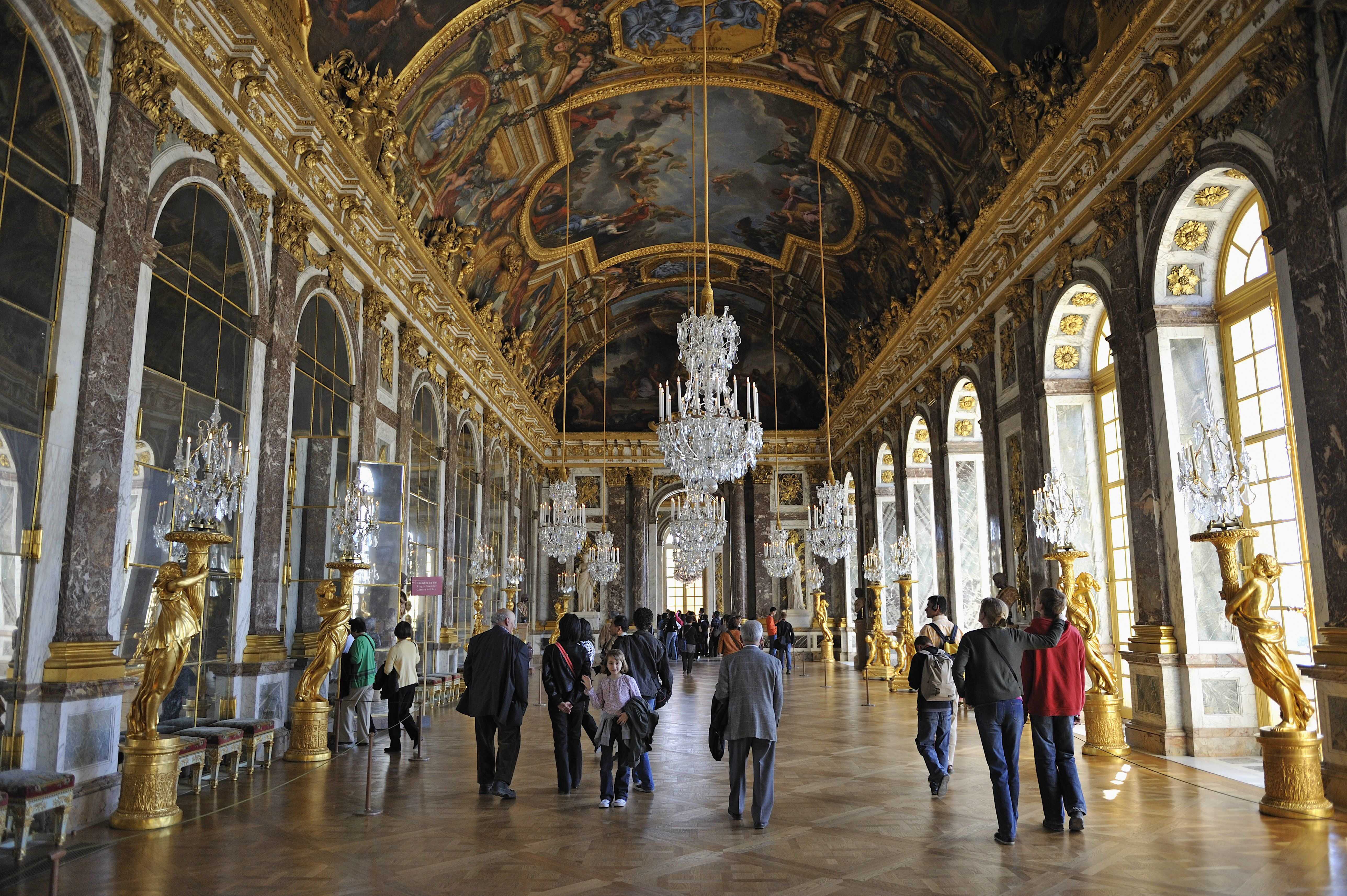 Large, Baroque marble hallway with statues and mirrors in the Palace of Versailles