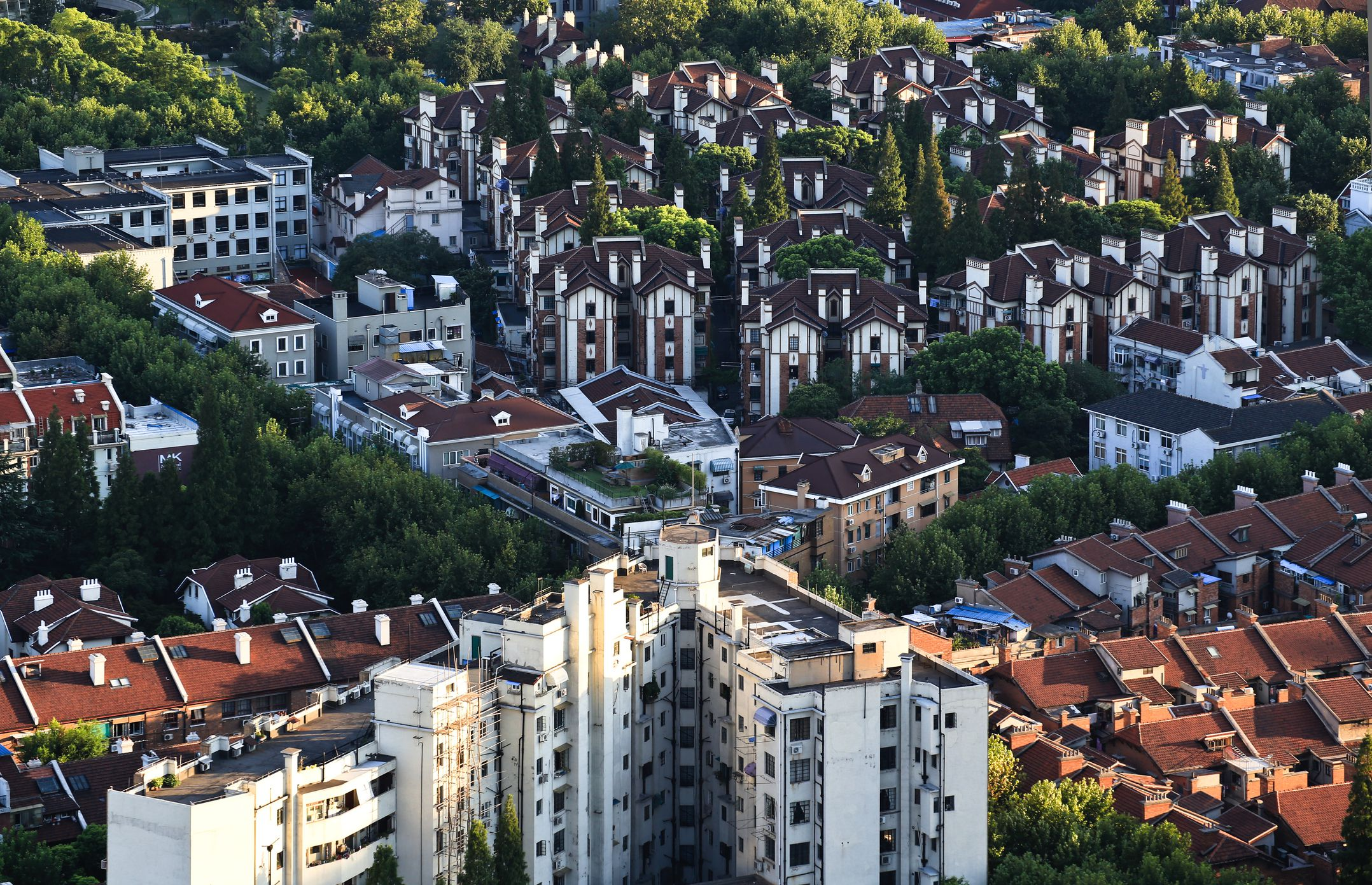 Aerial view of the formerly French concession in Shanghai, dotted with green forest against red terracotta roof