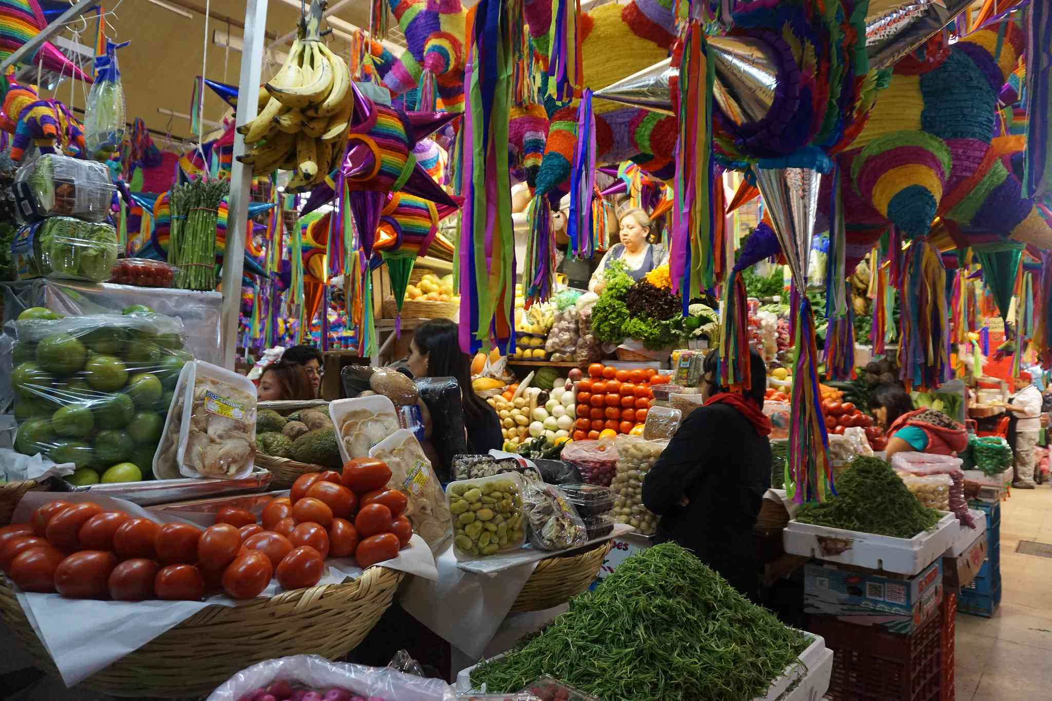 piles of fresh produce in a market with colorful piñatas overhead