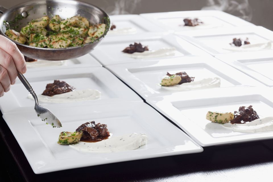 Chef plating dishes of lamb and artichokes
