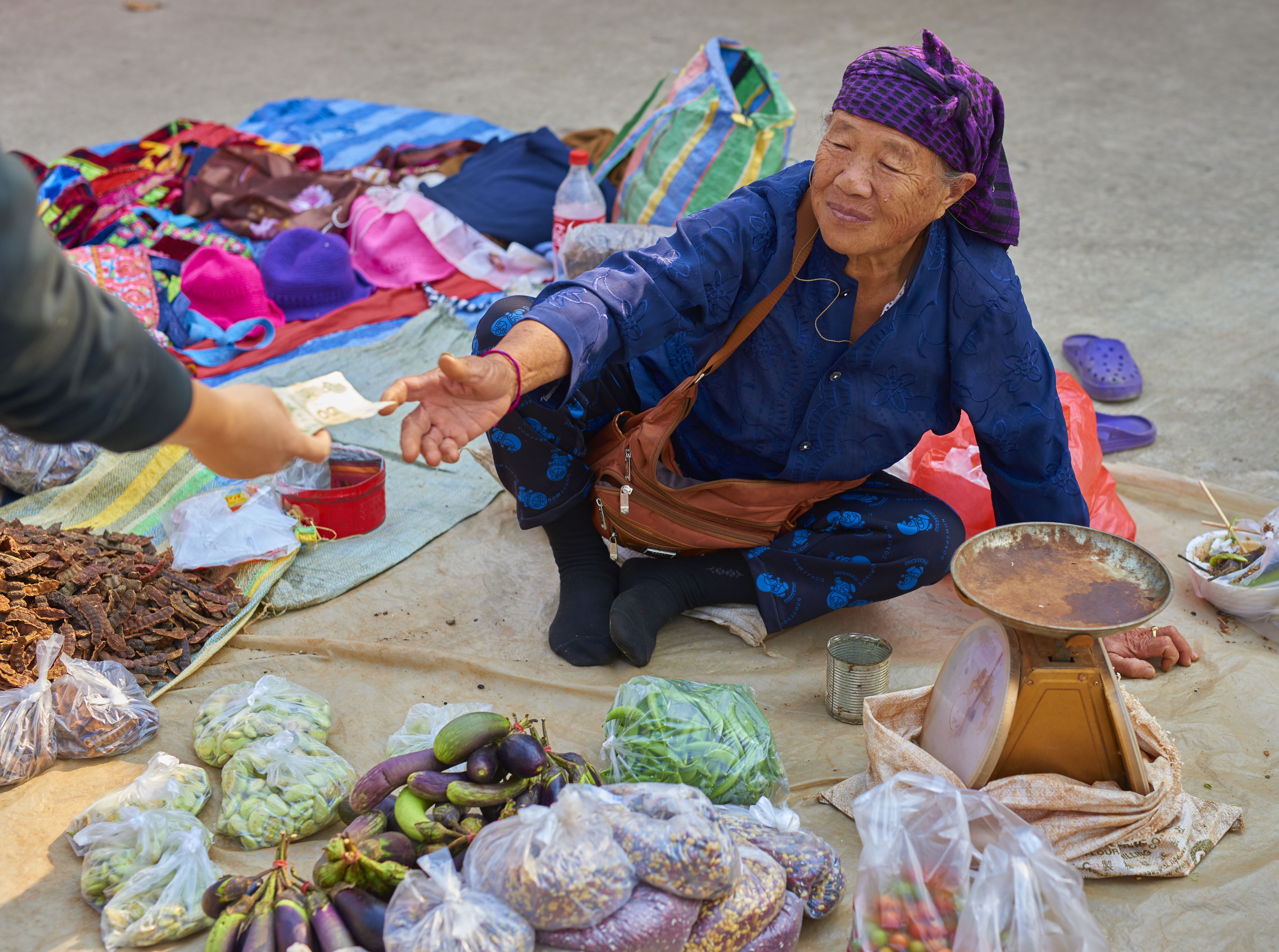 A merchant accepts money at the market in Pai