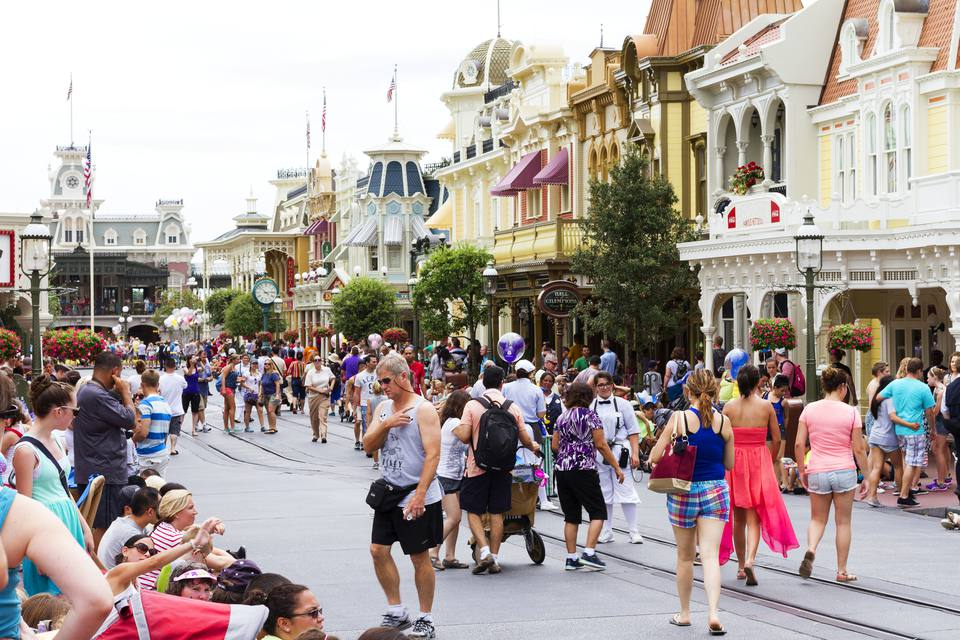 View of the people and families that cross Main Street USA, the entrance to Magic Kingdom amusement park at Walt Disney World with restaurants and souvenir stores. Shoot at mid day during the high summer season.