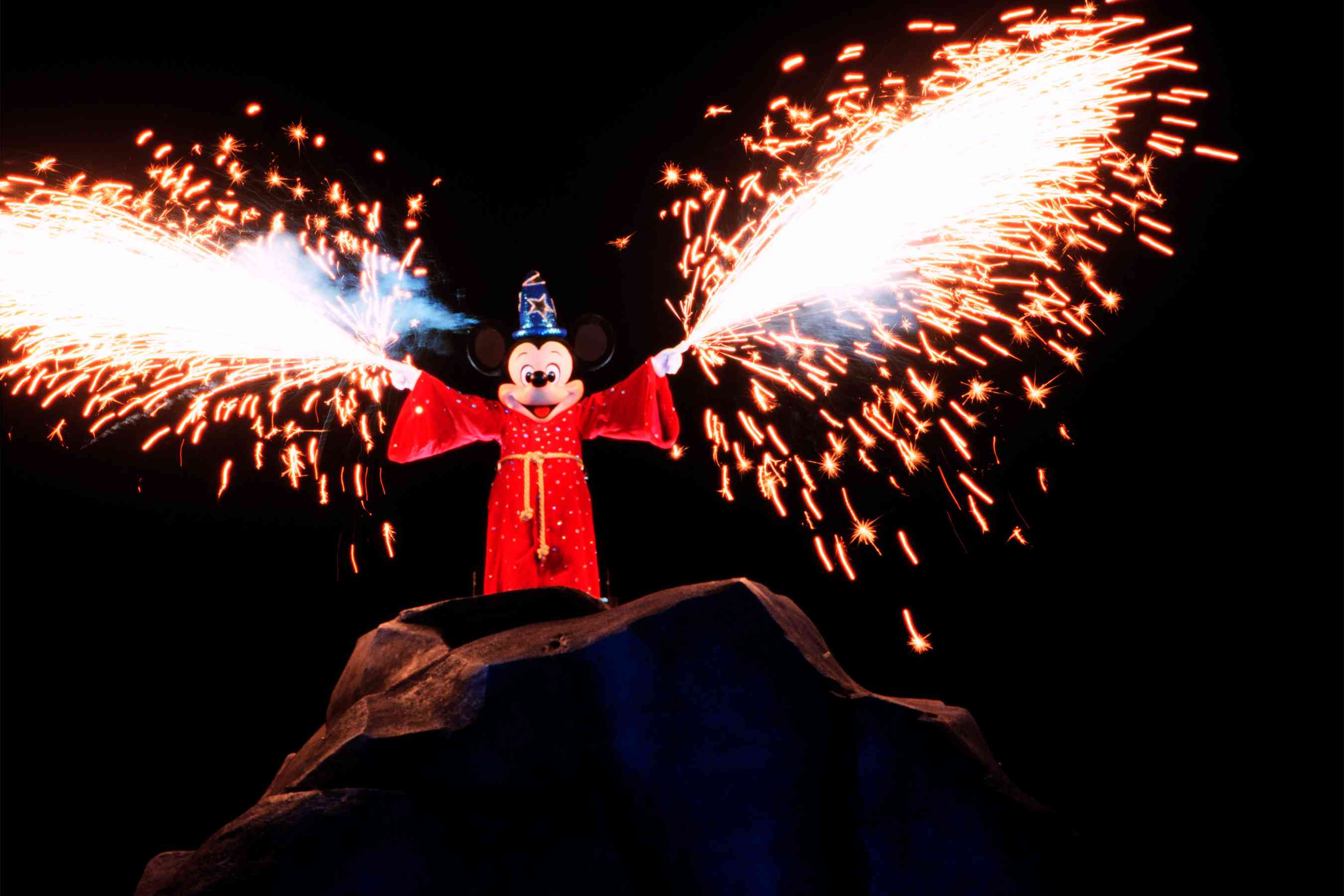 Wizard Mickey holding sparklers at the Fantasmic! show in Hollywood Studios