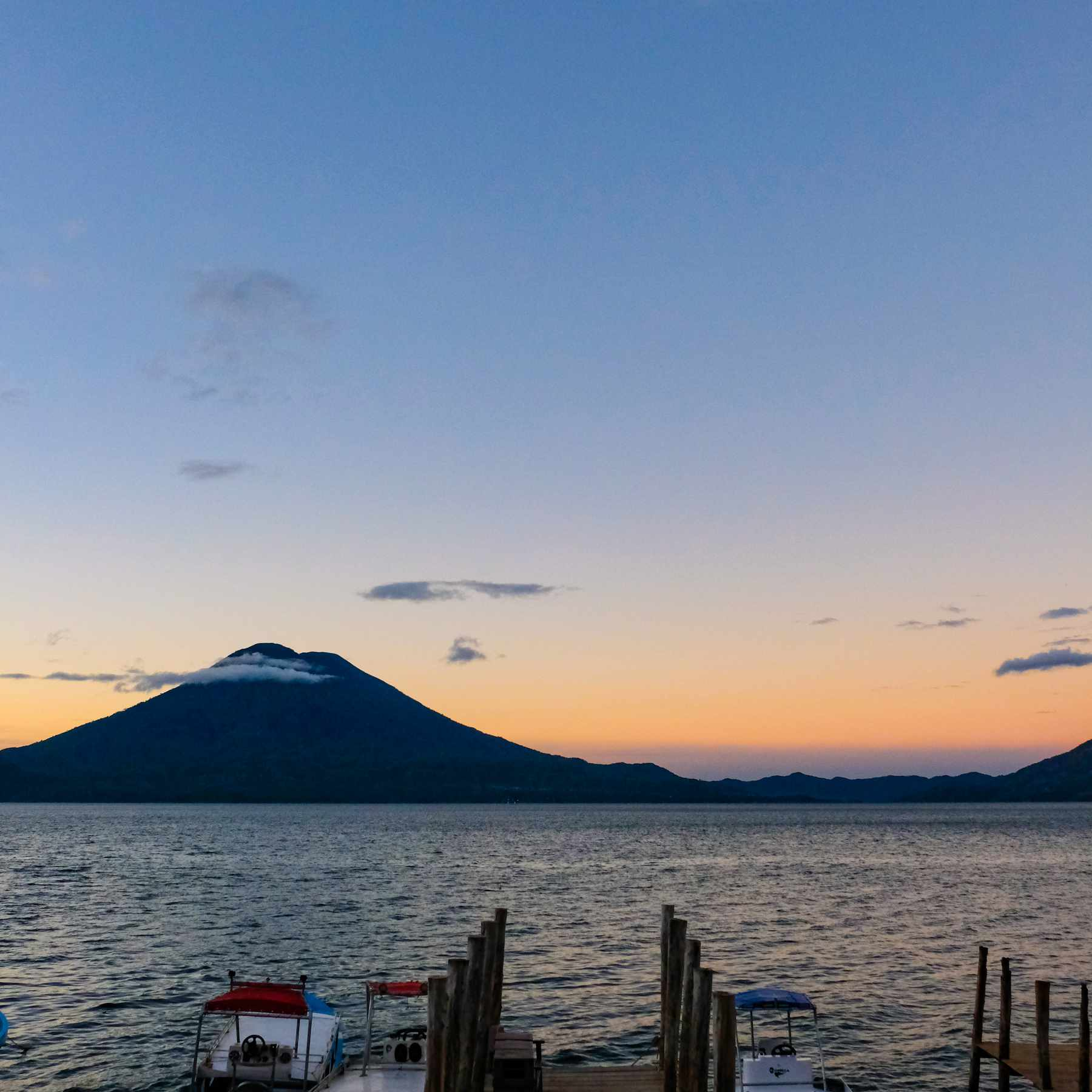 Boats docked on Lake Atitlan with a view of Atitlan volcano