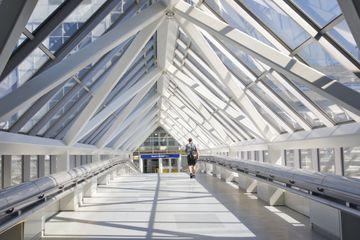 Man walking through glass and steel Skyway at Minneapolis-Saint Paul International Airport, Minnesota, Midwest, USA