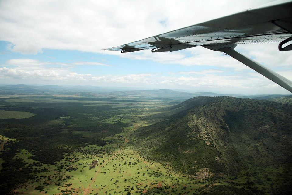 Wing of a small plane in flight above the Maasai Mara National Reserve, Kenya