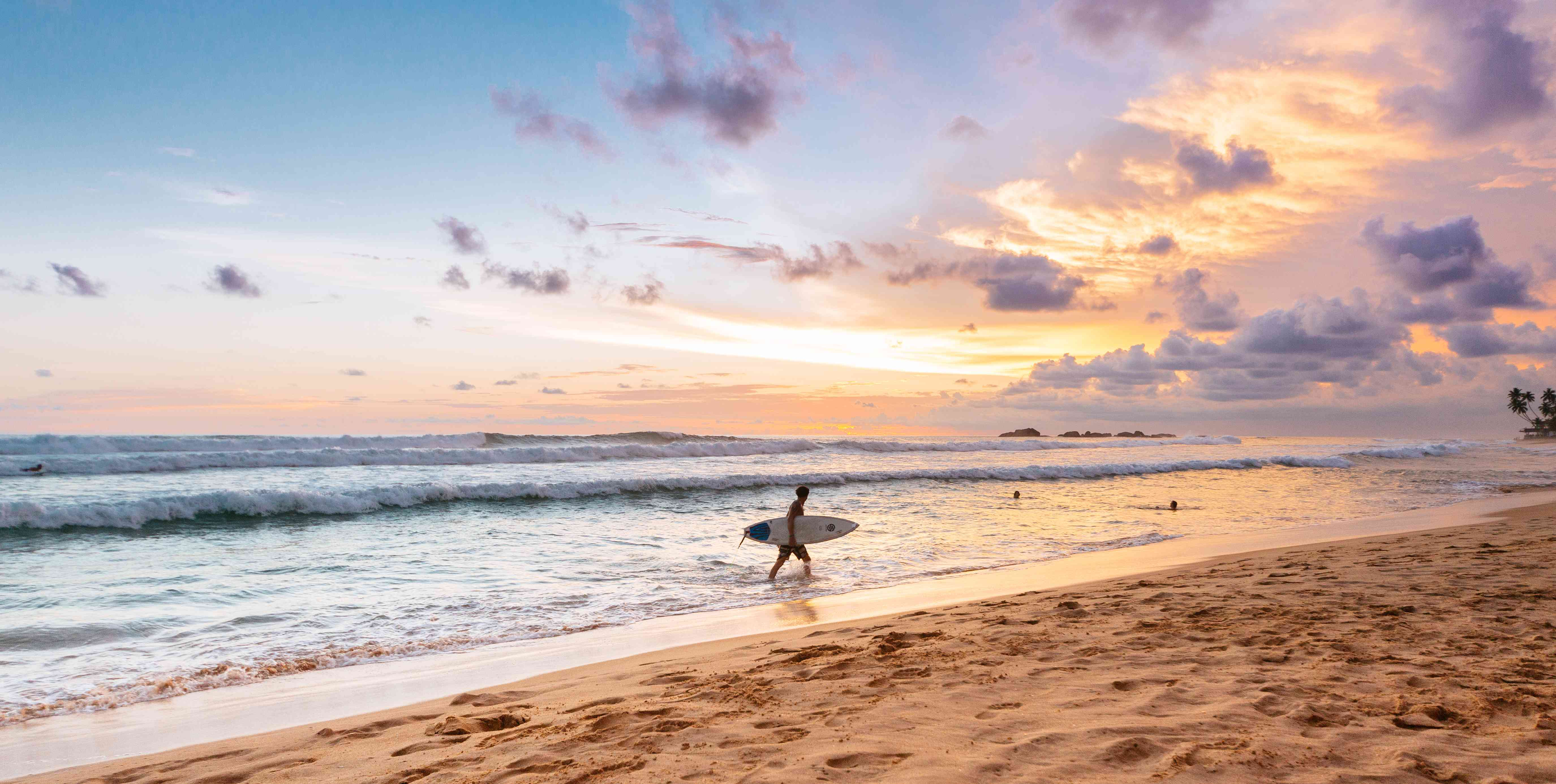 Surfer carries a board at sunset on Narigama Beach