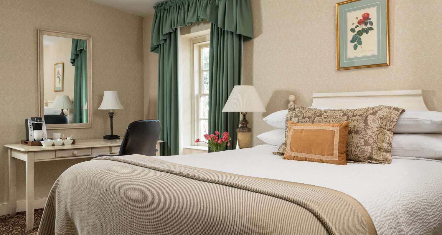 queen size bed in a hotel room with a desk and green curtains