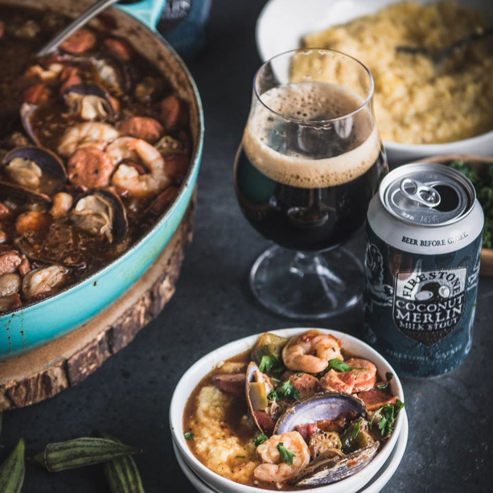 small bowl of seafood gumbo and grits with a glass of dark beer and a beer can. There is a large plate with grits behind the beer and a pan of gumbo to left of the beers