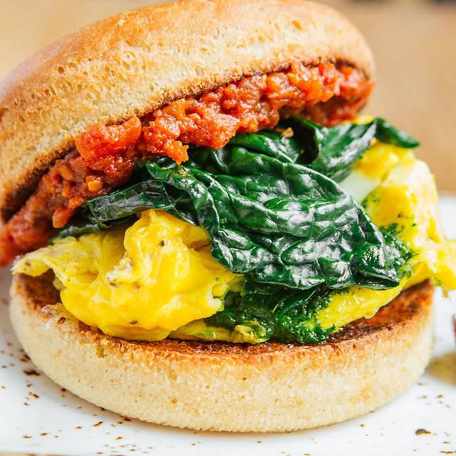 a sausage, egg, and spinach sandwich