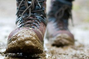 Close-up of hiking boots walking on a trail through the mud