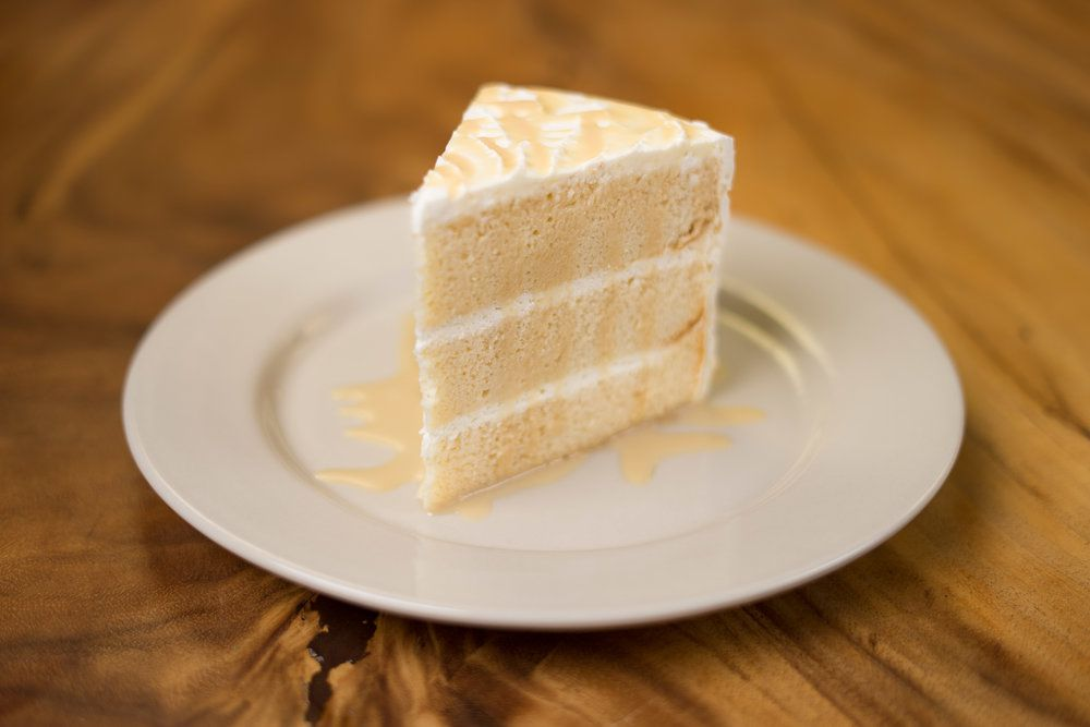 slice of a three layer cincos leches cake with white frosting on a white plate