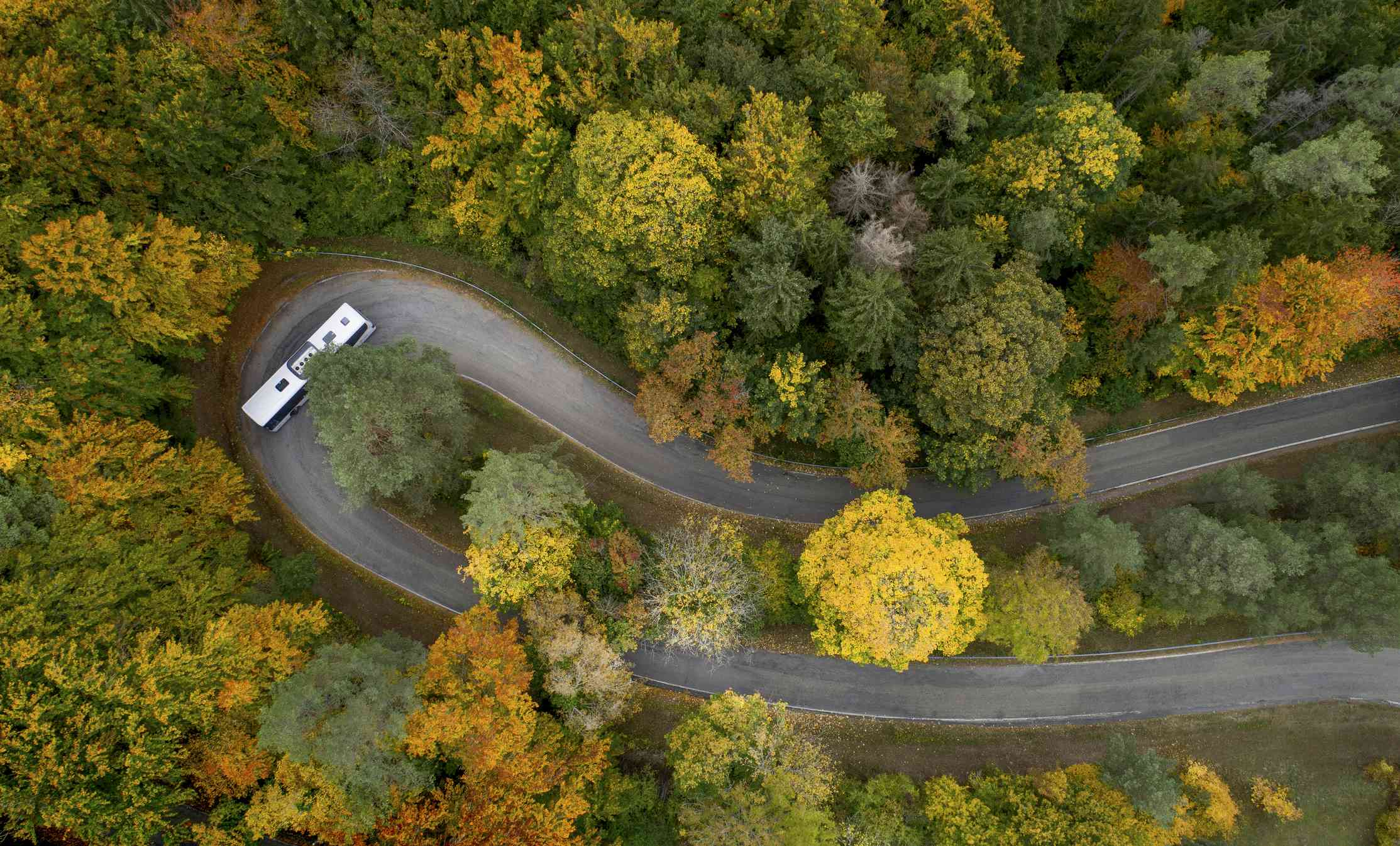 Hairpin curve on a country road in autumn with bus driving