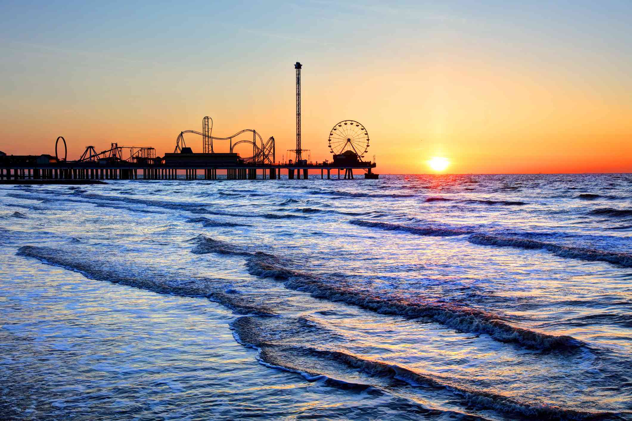 Galveston Island Historic Pleasure Pier in silhouette at sunset