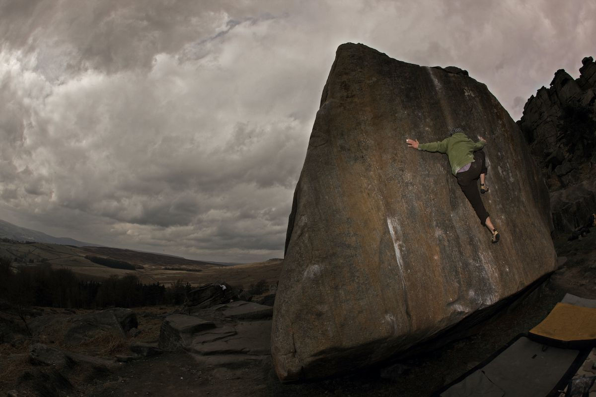 A climbers ascends the side of a boulder with dark gray, cloudy skies overhead.