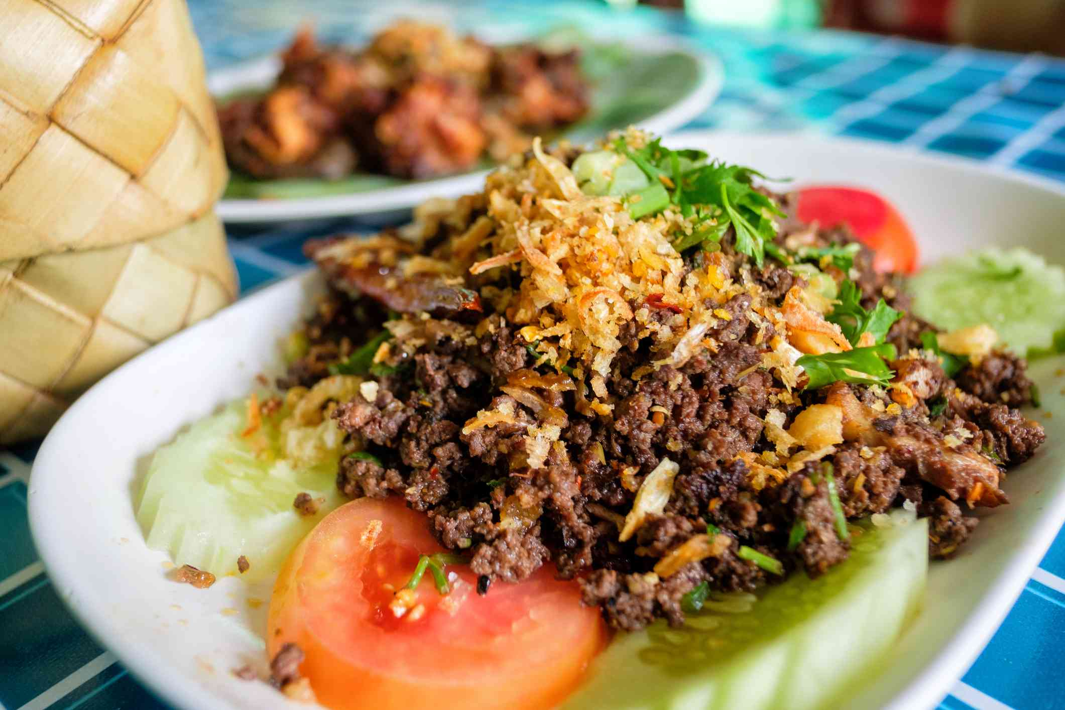 Larb kua on a plate with ground beef, cucumber and tomatoes