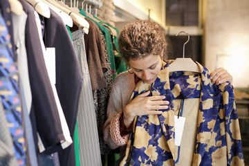 Young woman in a fashion store holding up blazer