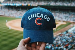 A picture of a Chicago Cubs hat, with Wrigley Field in the background