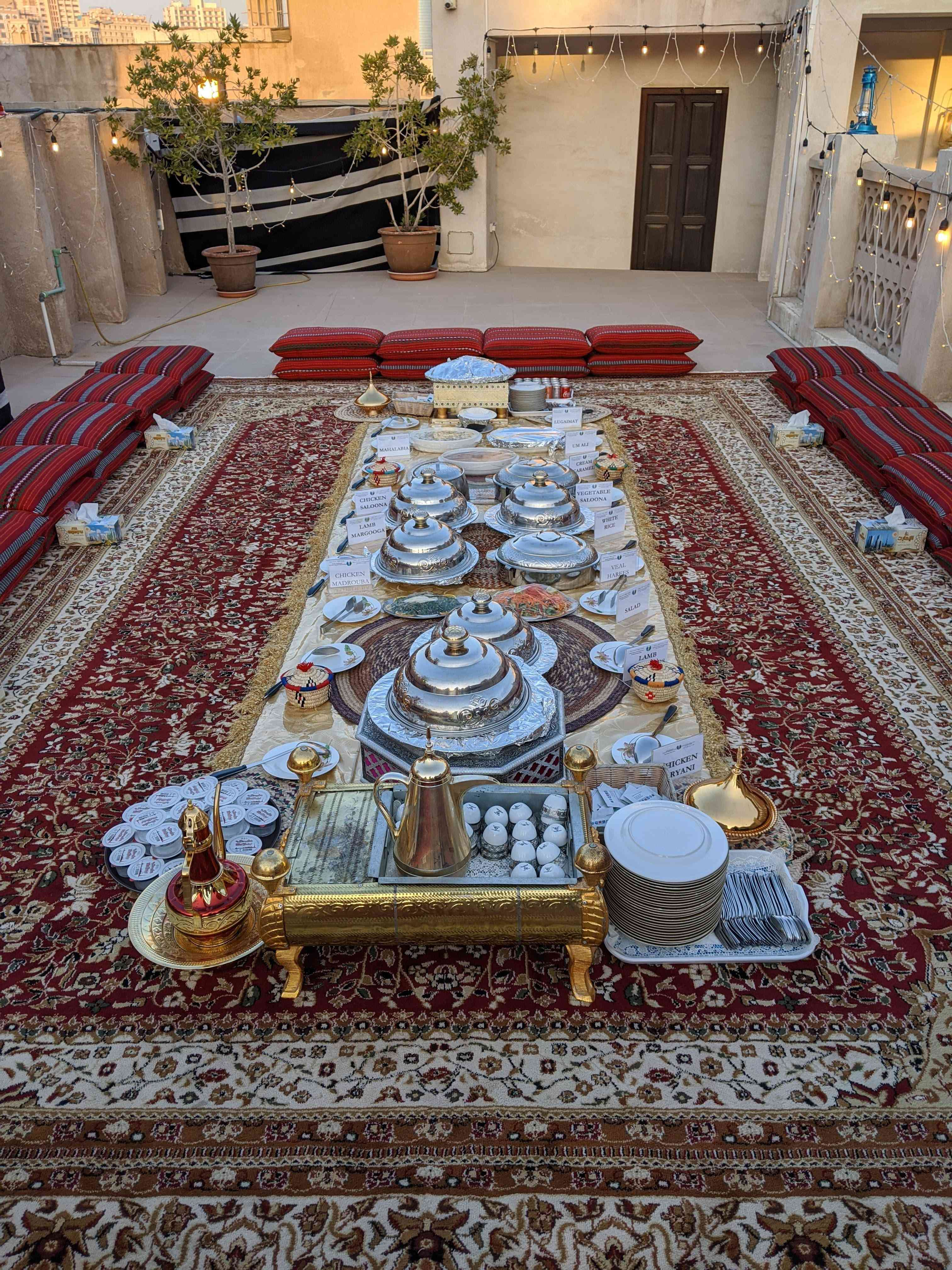 low table on an ornate rug set with plates and metal serving trays. there are red cushions around the perimeter of the rug