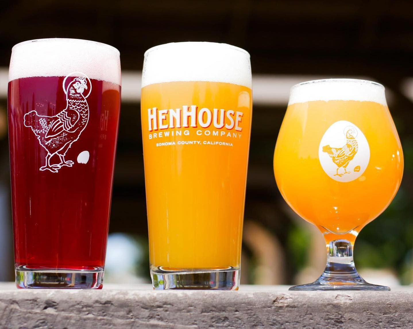 two pint glass and a stout glass in a line, filled with beer. the beer on the left side is pinkish red and the other two are honey-clored
