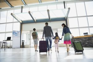 Family with suitcases leaving airport