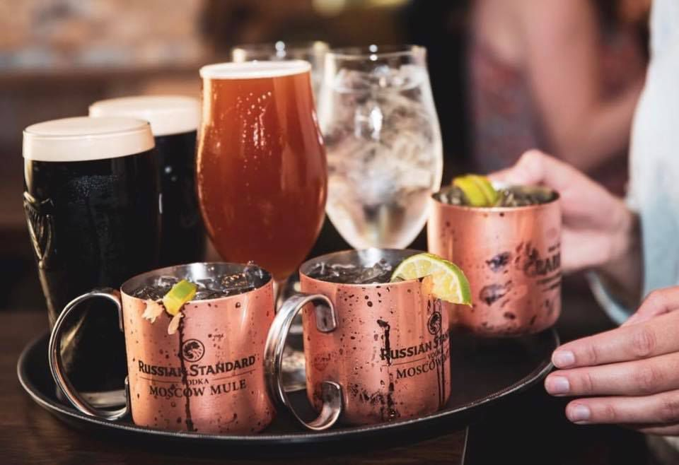 A round tray resting on a table with two caucasian hand touching side. On the tray are two pint glasses with a dark beer, three taller glasses — three with ice water and one with a pale ale — and three moscow mules with a lime slice on the rim