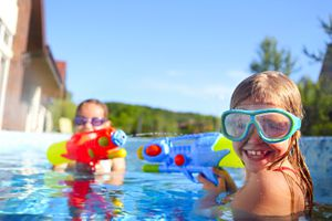 Two kids with water guns in pool