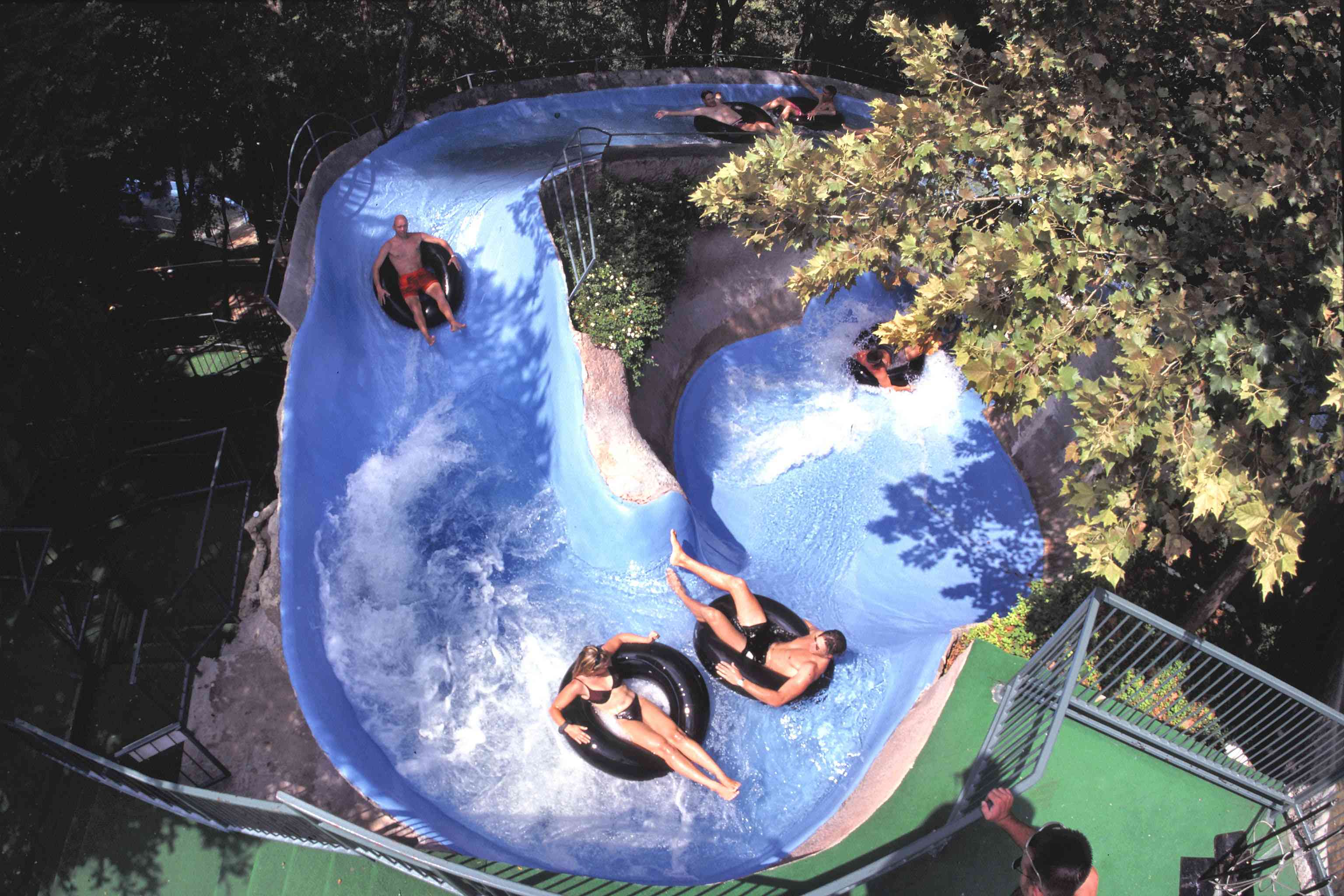 Water park guests floating down slide on tubes