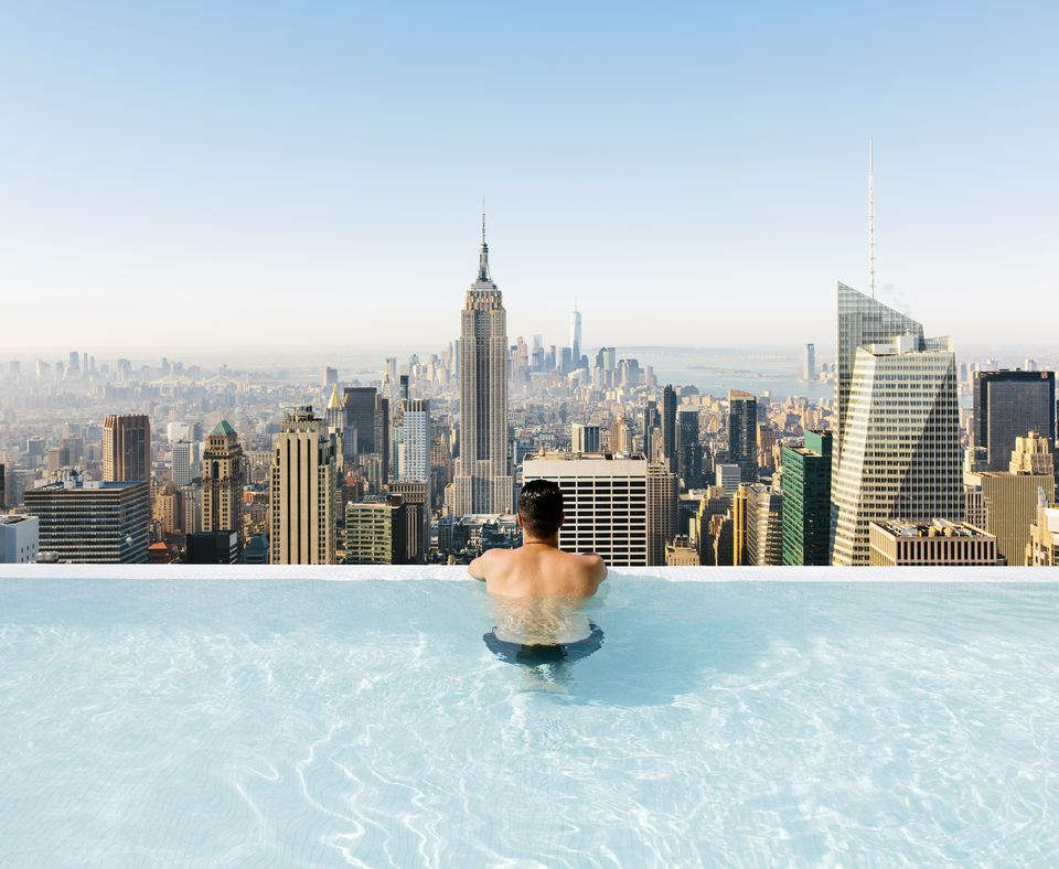 Young man relaxing in a swimming pool with view towards New York City skyline