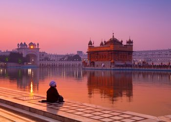A man observes the Golden Temple in Amritsar reflected in water at dawn
