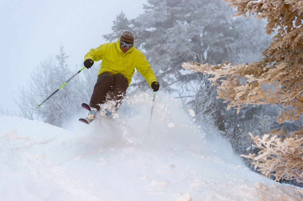 A skier jumps through fresh powder on an early morning run